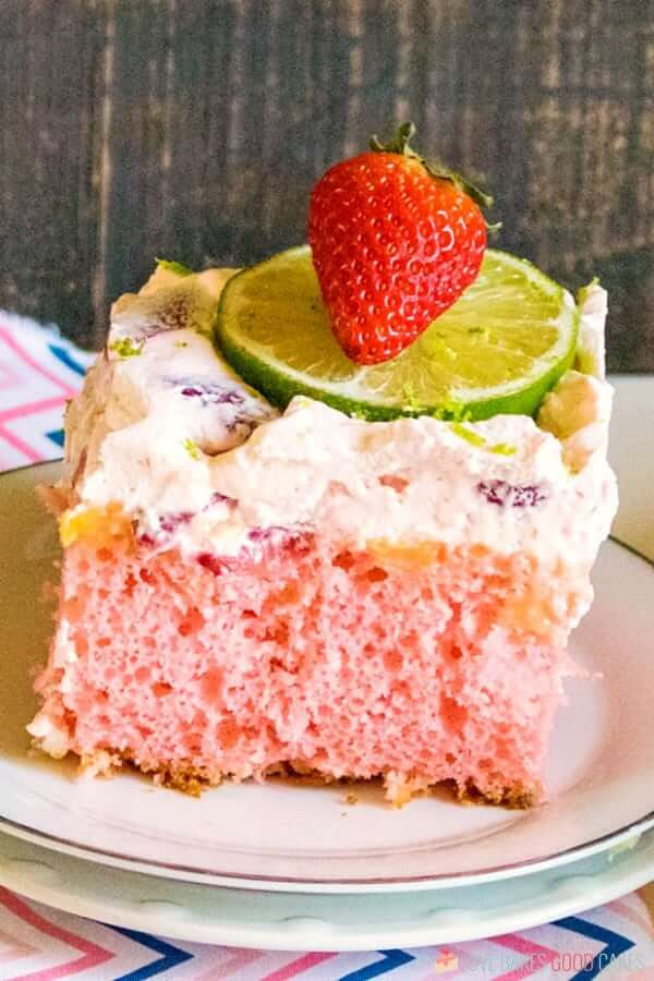 Boozy Strawberry Margarita Poke Cake on a plate with fresh fruit.