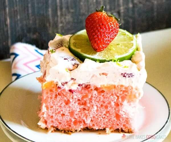 Boozy Strawberry Margarita Poke Cake on a plate with fresh fruit close up.