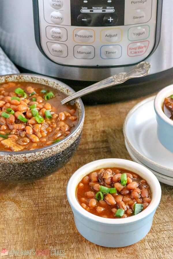 Instant Pot Baked Beans in two bowls with a spoon.