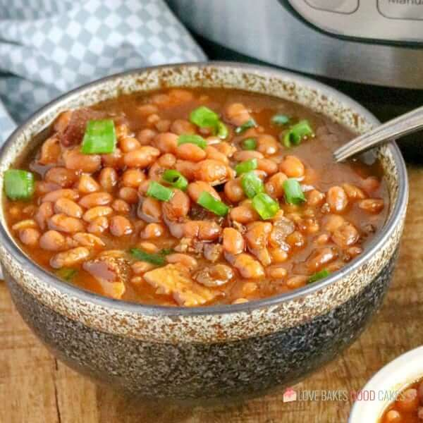 Instant Pot Baked Beans in a bowl with a spoon close up.