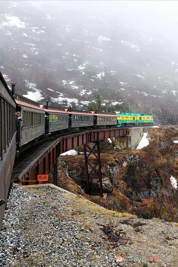 White Pass Railway descending down the mountain over a trestle bridge with snow and fog.