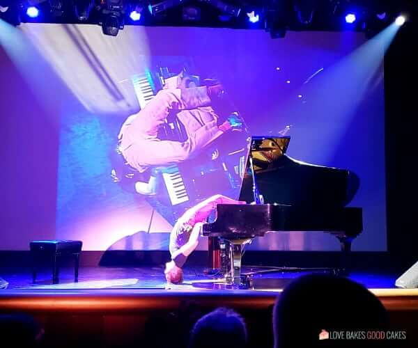A man playing a piano upside down on stage in the theater of a cruise ship.