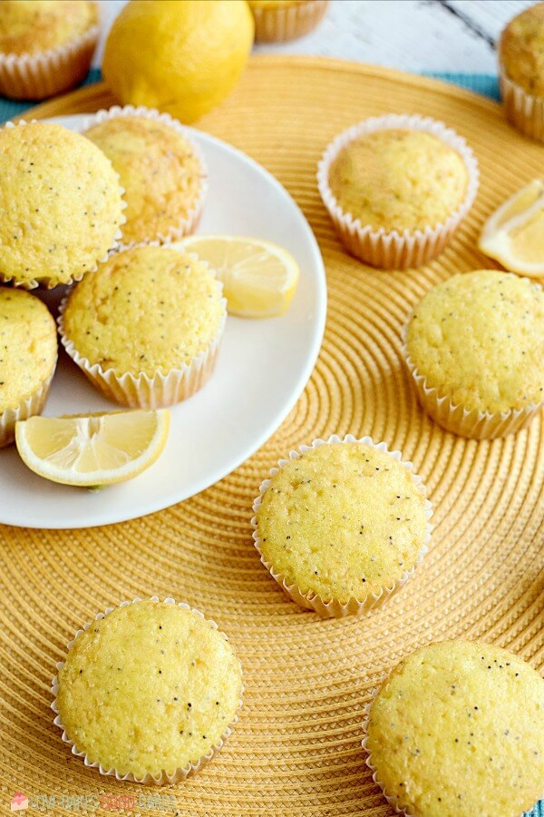 Lemon Poppy Seed Muffins piled up on a white plate with fresh lemon slices.