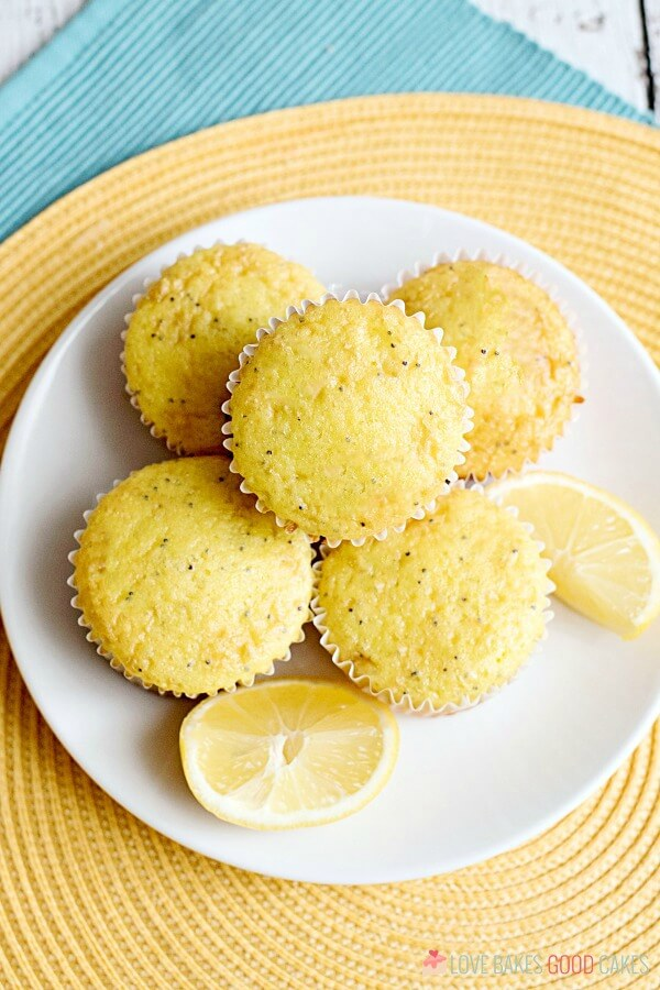 Lemon Poppy Seed Muffins piled up on a plate with fresh lemon wedges.
