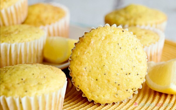 Lemon Poppy Seed Muffins piled up on a serving plate.