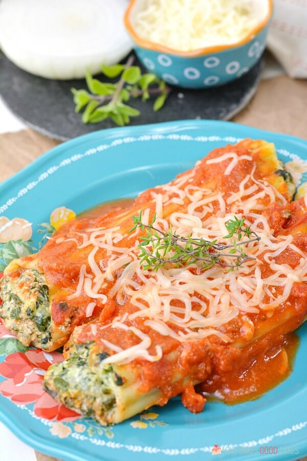 two Spinach Ricotta Manicotti on a blue plate
