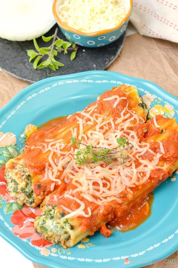 Spinach Ricotta Manicotti on a blue plate.