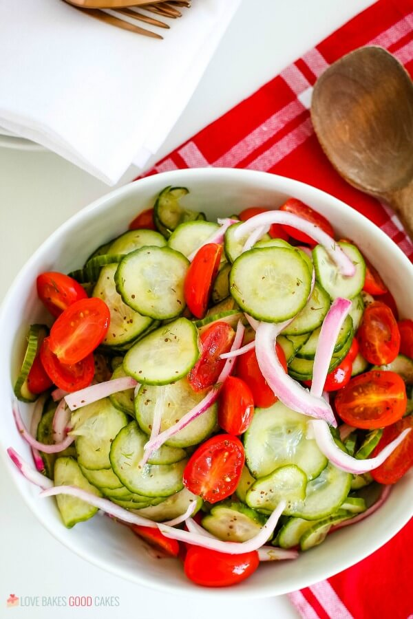 Zesty Cucumber Tomato Salad in a white bowl with red towel