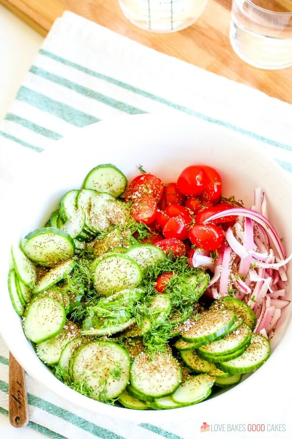 cucumbers, tomatoes, onions, and seasonings in bowl