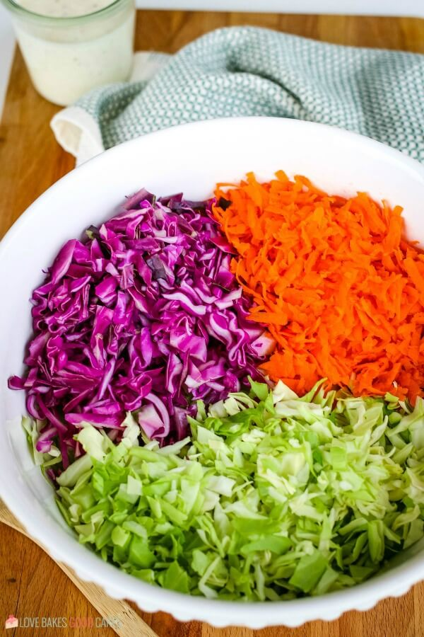 Purple and green cabbage and carrots in a mixing bowl for a coleslaw recipe.