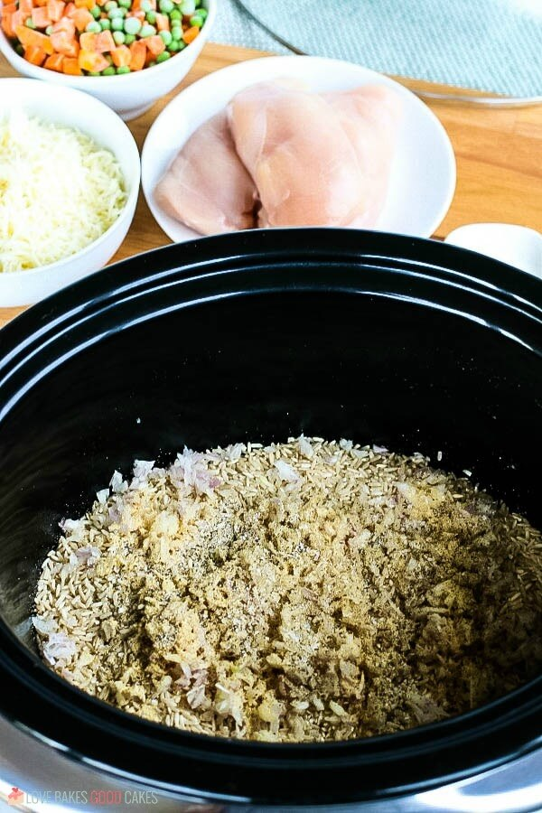 Brown rice and spices added to a slow cooker for chicken and rice.