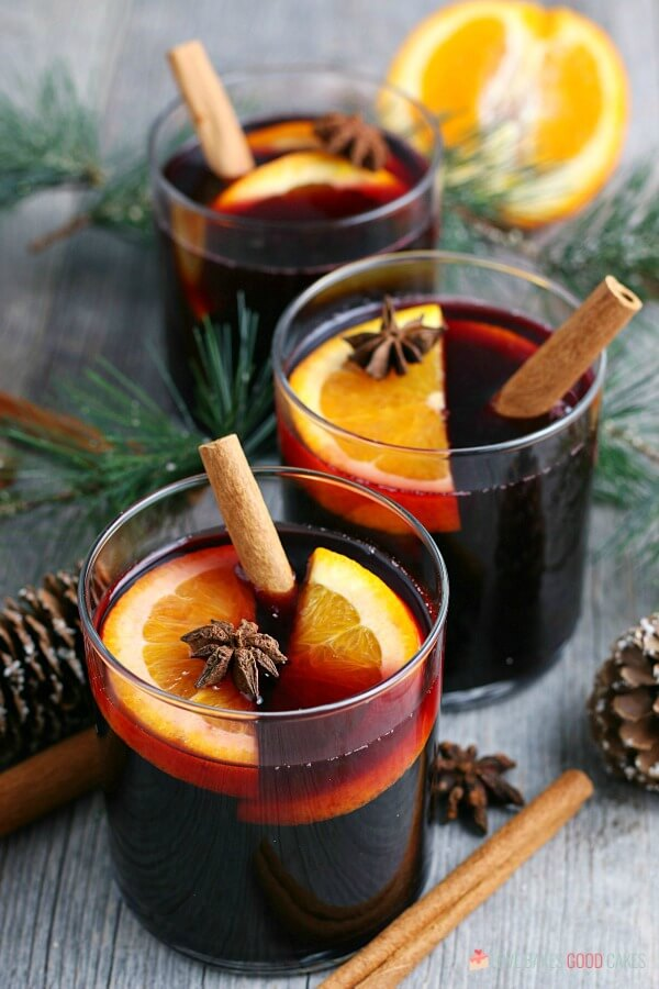 Here we see three glasses of the mulled wine recipe garnished with cinnamon sticks, orange slices, and star anise.