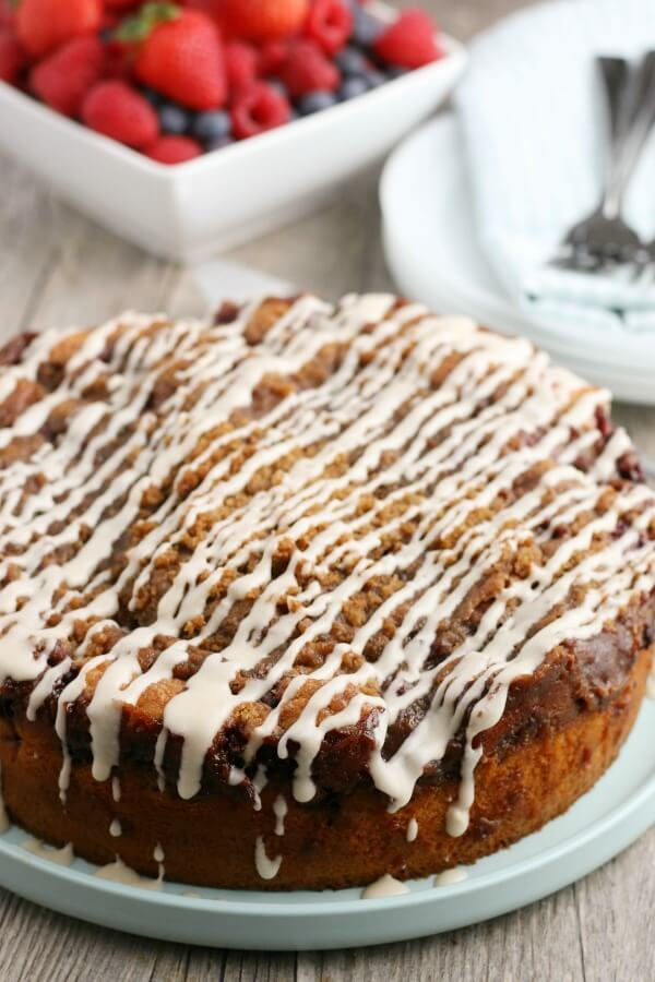 Whole Coffee Cake with Icing, berries and plates inthe background