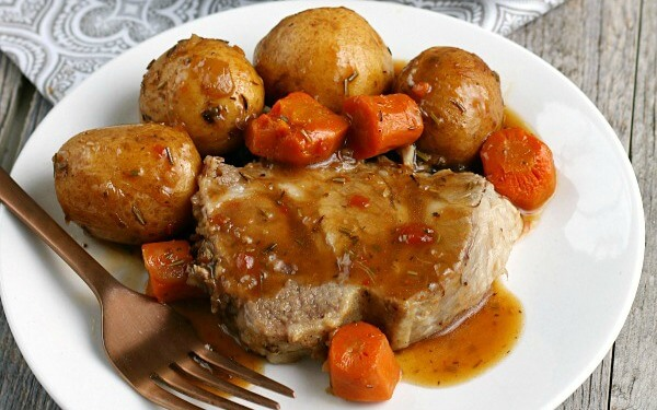 finished and sliced pork loin roast with veggies and potatoes.