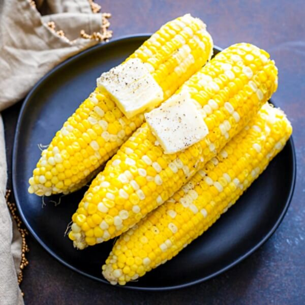 cooked corn on the cob with butter on black plate