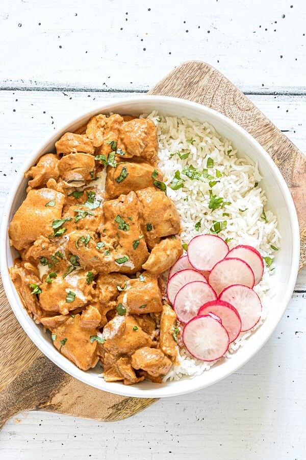 Instant Pot Butter Chicken in white bowl with rice and sliced radishes