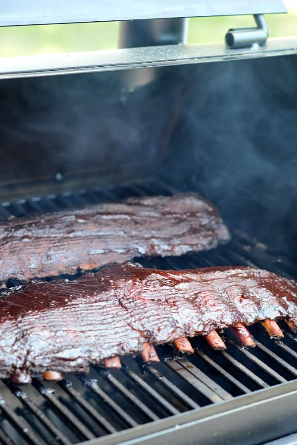 Two racks of ribs being smoked on the grill