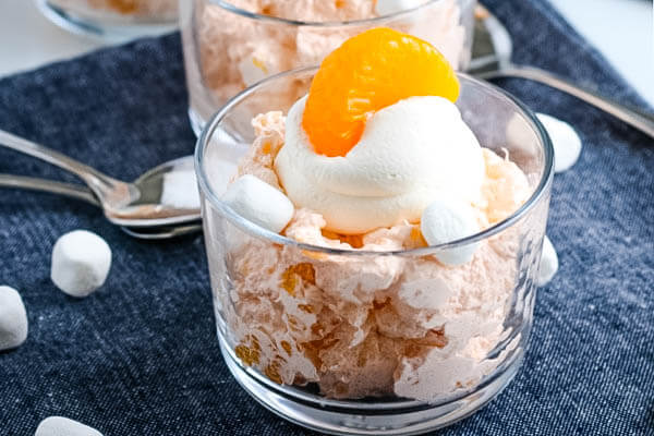 Mandarin Orange Fluff Salad in small glass bowl garnished with whipped topping and mandarin orange