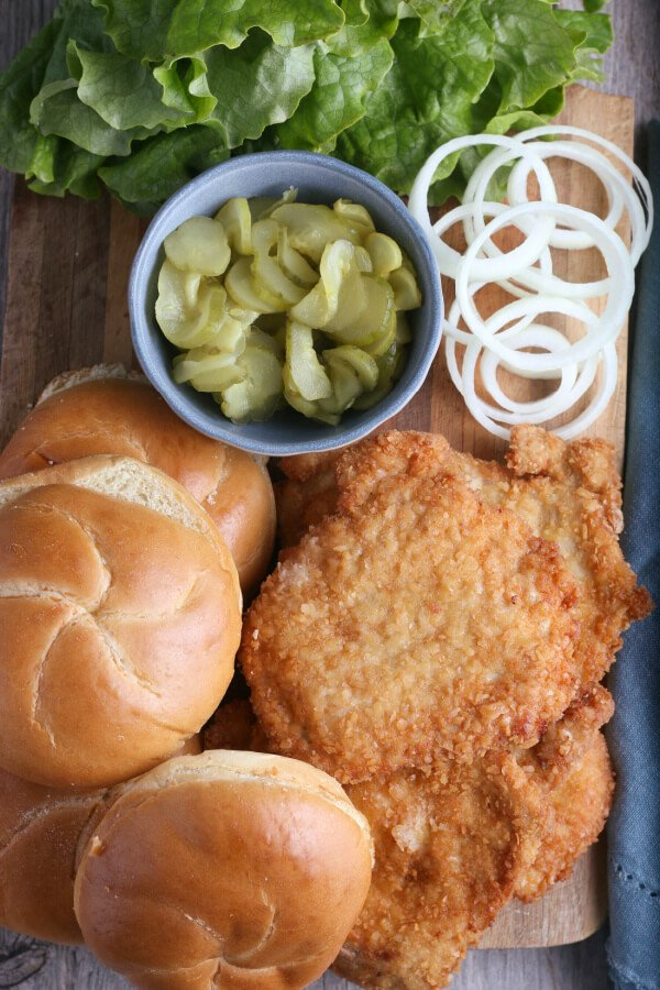 finished ingredients laid out on a cutting board to make breaded pork tenderloin sandwich