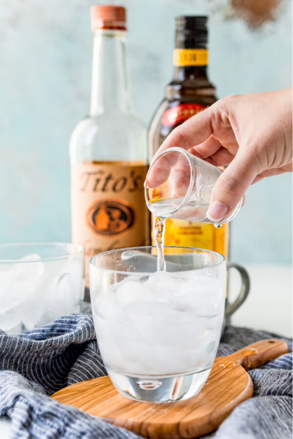pouring vodka into glass over ice