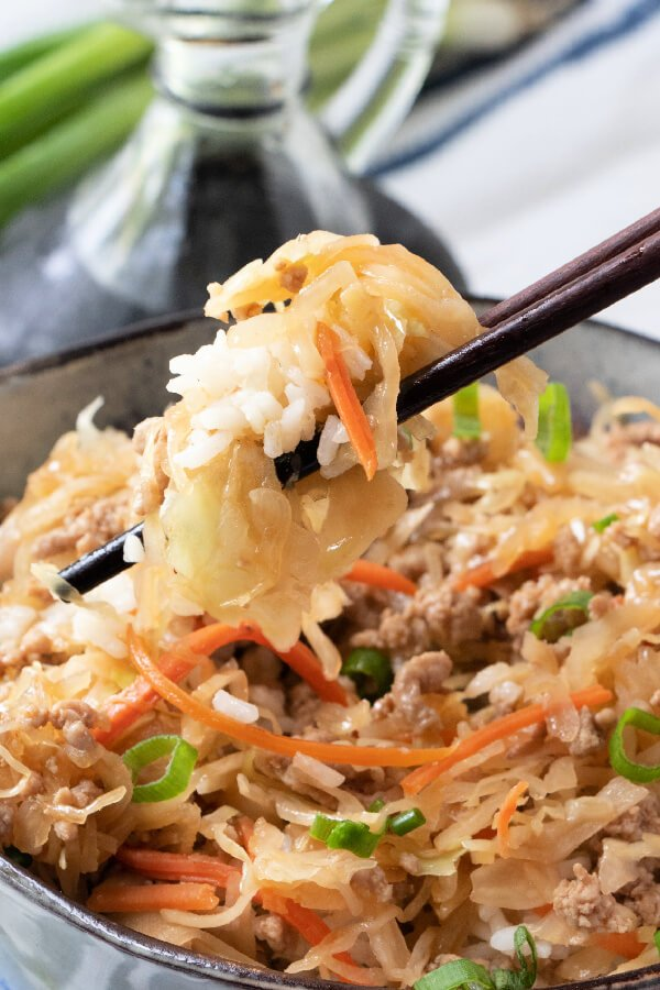 chopsticks holding rice with egg roll in a bowl