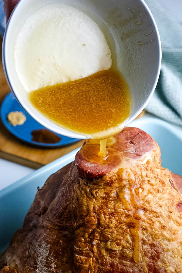 pouring honey and butter mixture over a spiral ham