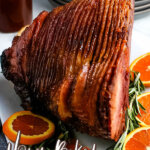 honey baked ham on serving platter with orange slices and rosemary sprigs