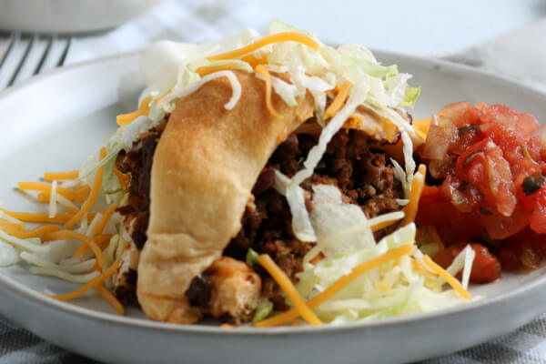 slice of taco ring with shredded lettuce cheese and salsa
