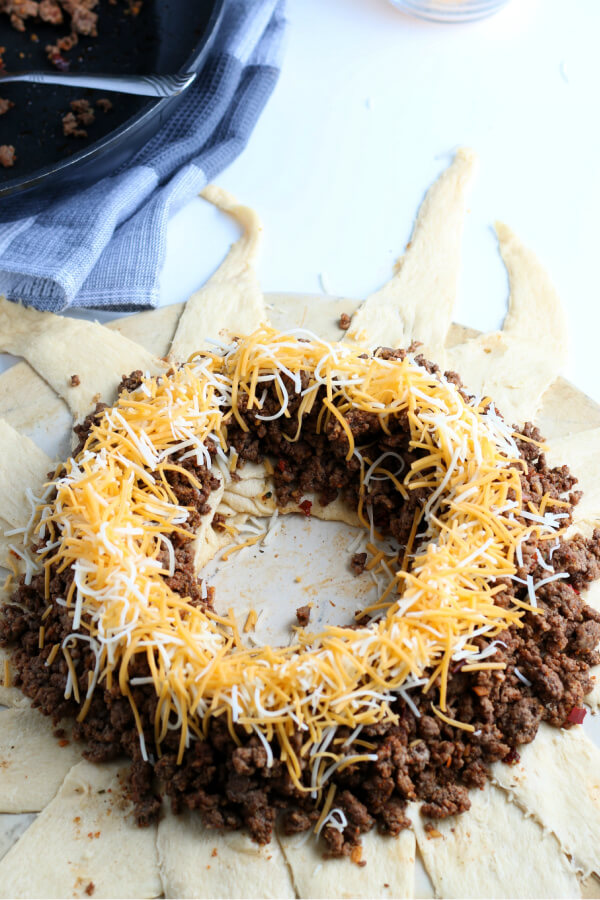 shredded cheese on top of the seasoned ground beef