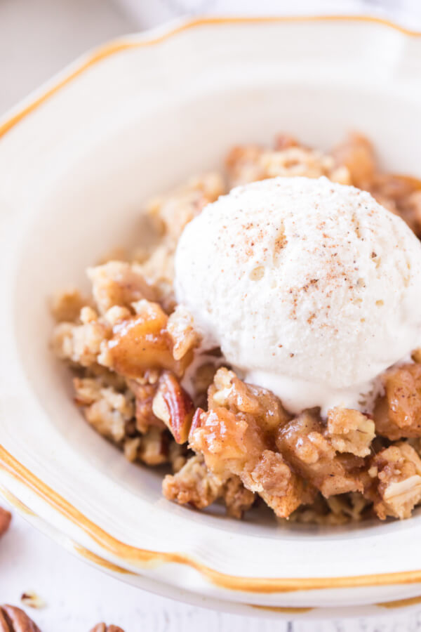 portion of apple crumble in bowl topped with ice cream scoop