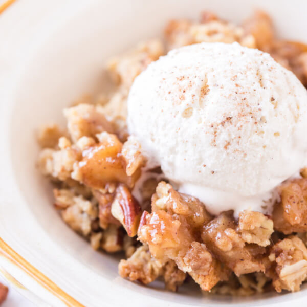 apple crumble in bowl with scoop of ice cream