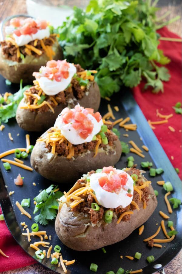 four potato tacos on black plate