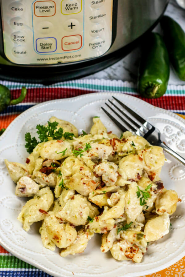 Instant Pot Chicken Jalapeno Popper Pasta on white plate with instant pot in background