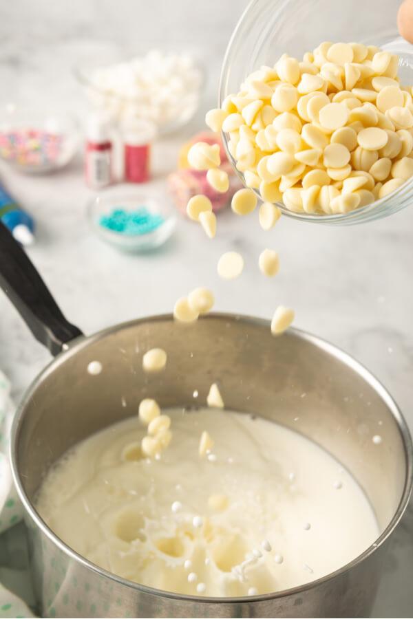 adding white chocolate to milk in pan