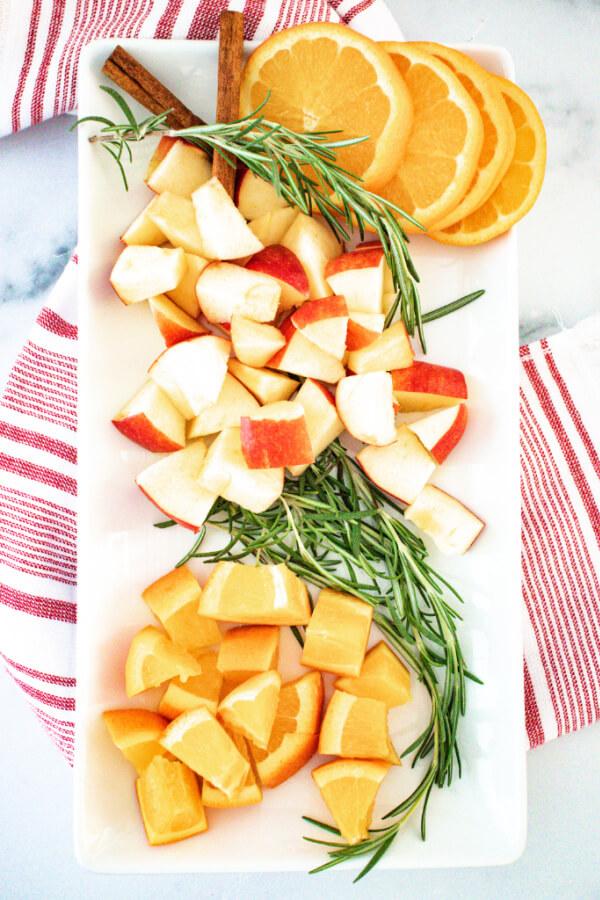 fruit, rosemary, and cinnamon sticks on plate