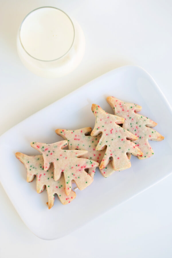 tree-shaped cookies on white plate with a glass of milk