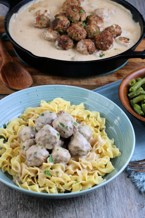 finished dish in the foreground with a pan of meatballs and gravy in the background