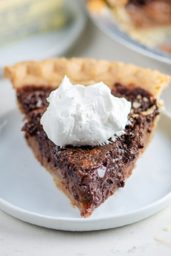 chocolate chess pie with a dollop of whipped cream on a white plate