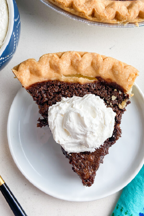looking down on a slice of chocolate chess pie with whipped cream on top
