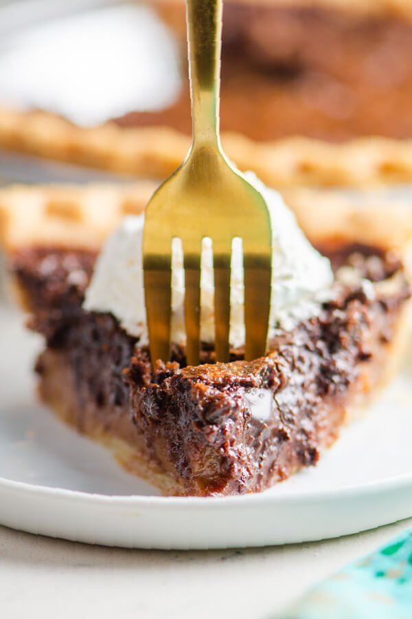 a fork taking off a bite of pie from the slice