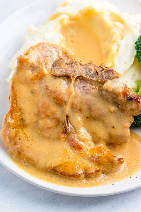 pork chop with gravy next to mashed potatoes with gravy