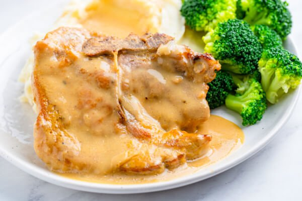 baked pork chop on plate with steamed broccoli