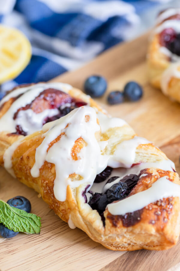 lemon blueberry danish on wooden board with fresh blueberries and blue linen