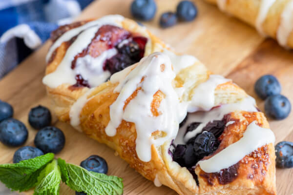 lemon blueberry danish on wooden cutting board with fresh blueberries
