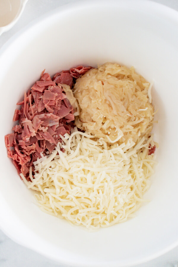 corned beef, sauerkraut, and swiss cheese in mixing bowl