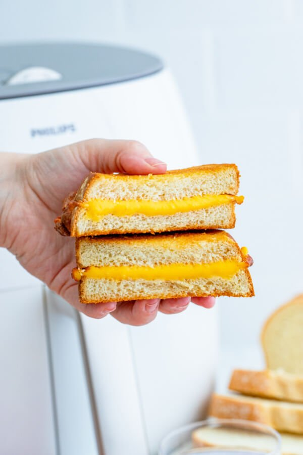 hand holding a sandwich cut in half with a white air fryer in background