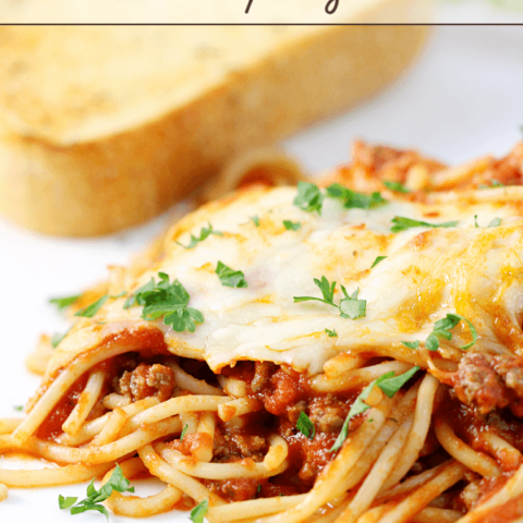 Cheesy Baked Spaghetti on a white plate with a slice of French bread.