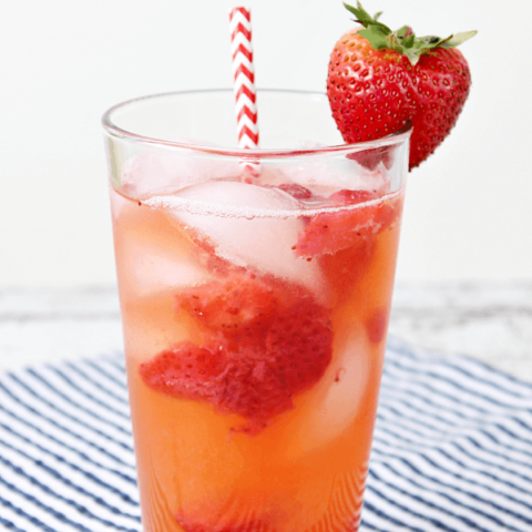 Copycat Red Robin Freckled Lemonade in a glass with a strawberry and a straw.
