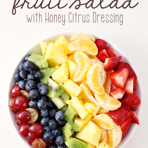 Rainbow Fruit Salad with Honey Citrus Dressing in a white bowl.