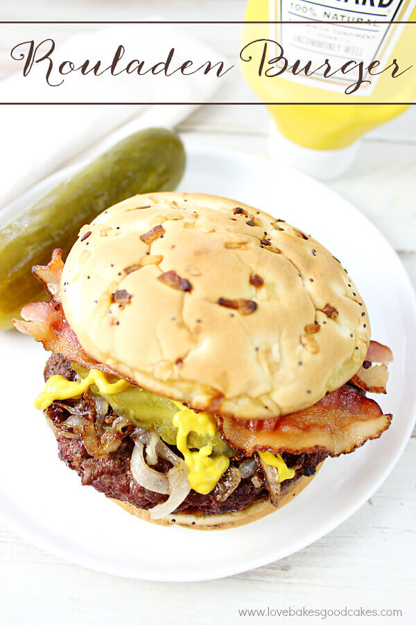 Rouladen Burger on a white plate with a pickle.